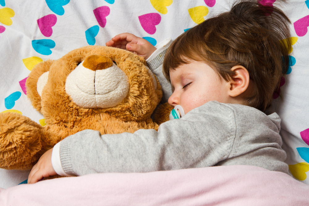 Child cuddling teddy